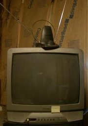 "A television with a VHF ""rabbit ears"" antenna and a loop UHF antenna."
